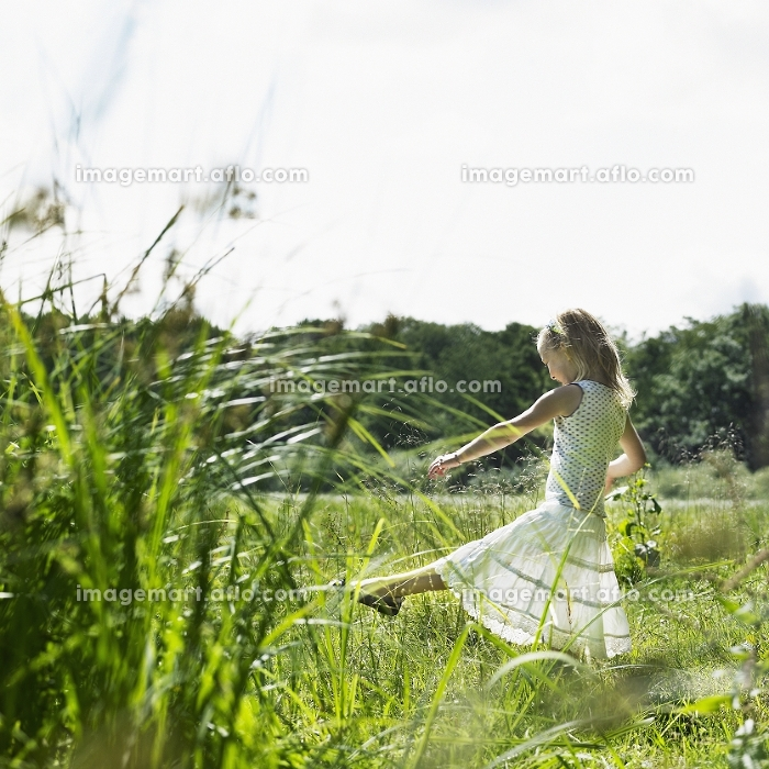 Girl playing in tall grass in fieldの販売画像