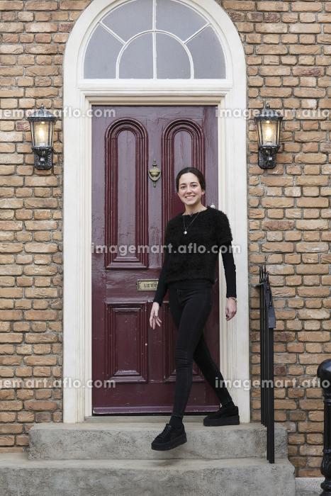 家の前に立つ外国人の若い女性の販売画像