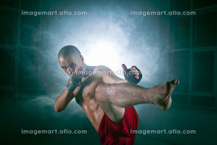 The young man kickboxing in blue smokeの販売画像