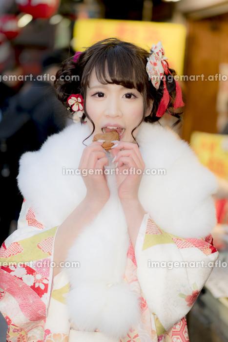 人形焼きを食べる振袖の女性