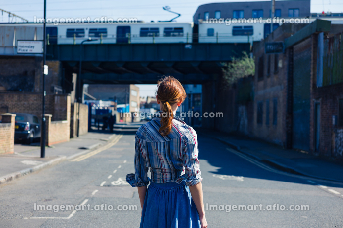 A young woman is walking in the street near a train bridge