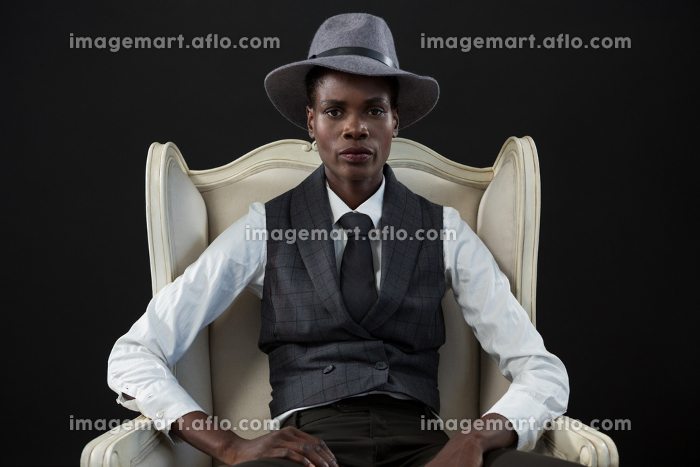 Androgynous man sitting on a chairの販売画像