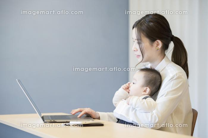 赤ちゃんを抱えてノートパソコンを操作する女性の販売画像