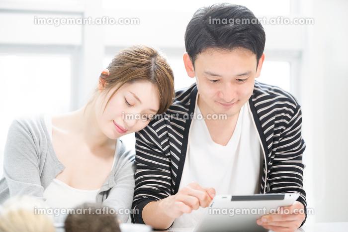 タブレットPCを使う夫の肩に寄りかかり眠る妻の販売画像