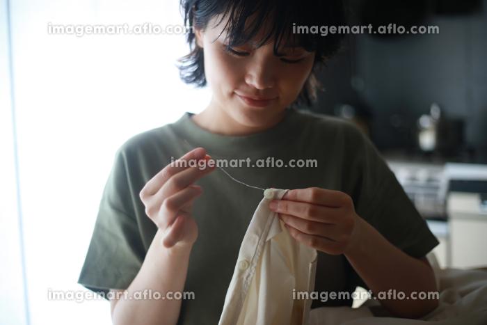 服にボタンを付ける女性の販売画像