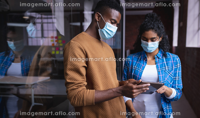 Diverse male and female colleagues at work discussing and looking at tablet wearing face masks. independent creative design business during covid 19 coronavirus pandemic.の販売画像