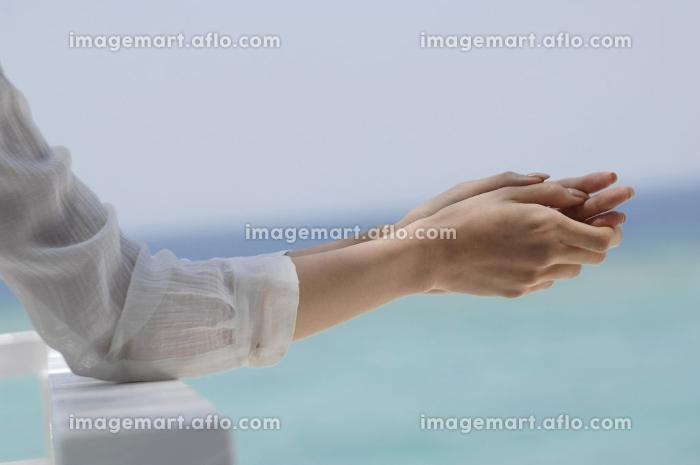 美しい海を見ている女性の手の販売画像