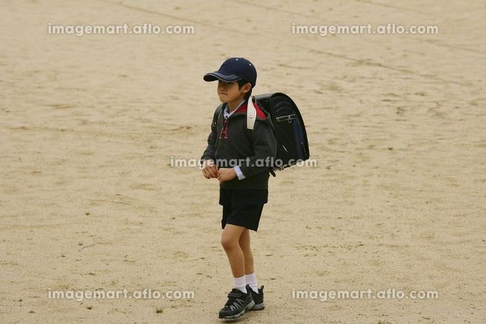 運動場を歩く小学生