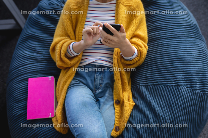 Midsection of businesswoman chilling in office relaxing space lying in beanbag using a smartphone. independent creative design business.の販売画像
