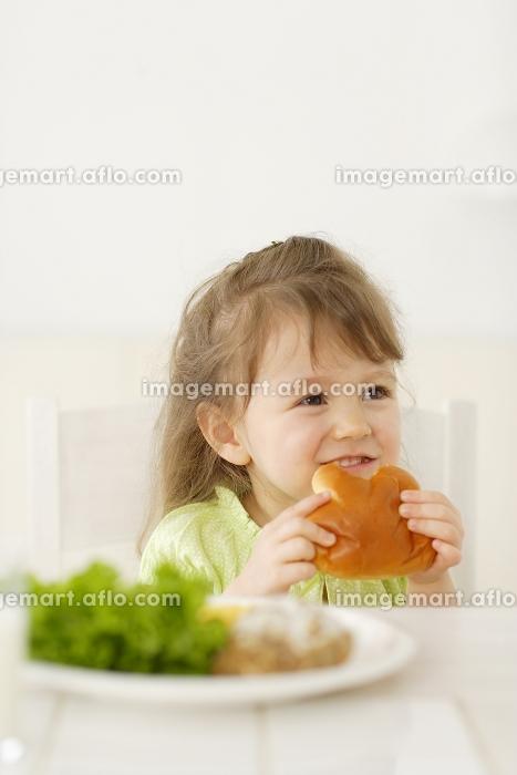 ダイニングでパンを食べるハーフの女の子の販売画像