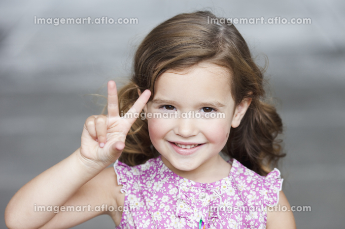 young girl holding up three fingersの販売画像
