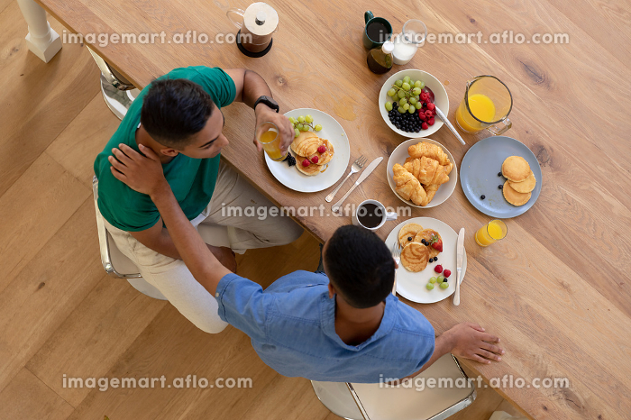 Diverse gay male couple eating breakfast together and talking. staying at home in isolation during quarantine lockdown.の販売画像