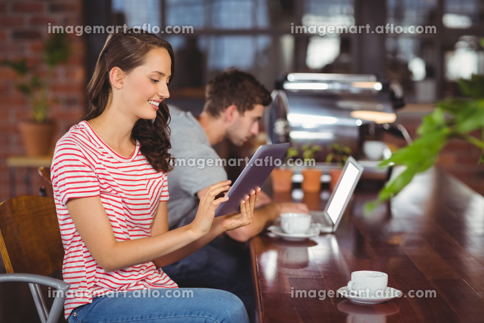 Smiling young woman using tablet computerの販売画像