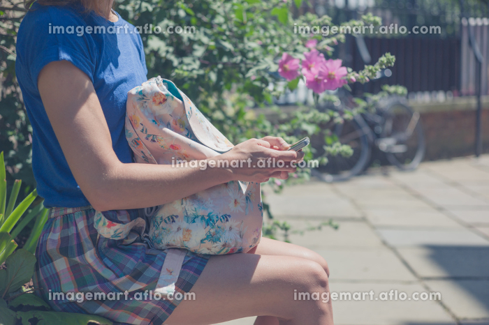 A young woman is sitting on a wall by some flowers and is using her smart phone on a sunny dayの販売画像