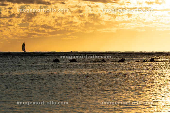 Sailboat drifts on the ocean at sunset in hawaiiの販売画像
