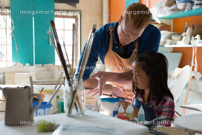 Male potter assisting girl to paint bowl