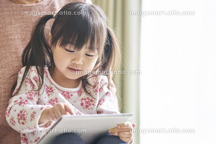 祖父母とタブレットを見る女の子