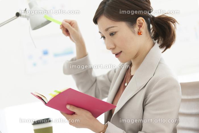 スケジュールの確認をするビジネスウーマンの販売画像