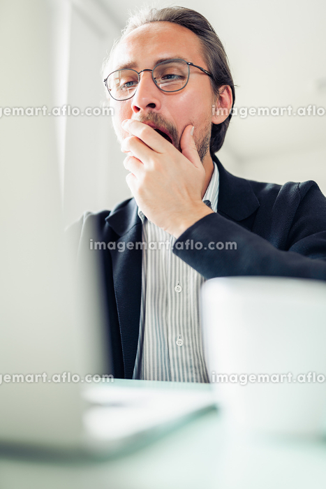 Tired young handsome man is yawning while working at the computer