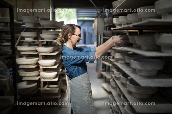 Female potter placing bowl in shelf