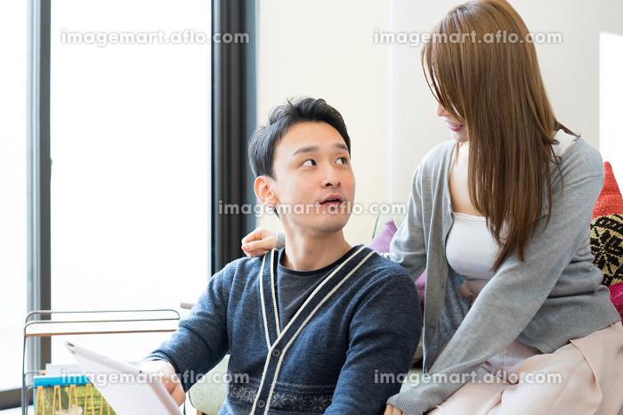 タブレットPCを見る笑顔の幸せなカップルの販売画像