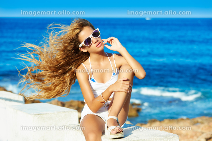 Blond kid teen girl on the beach long with curly hair waving at windの販売画像