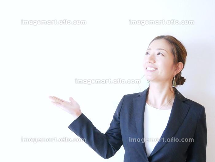 スーツを着て手を挙げている女性の販売画像