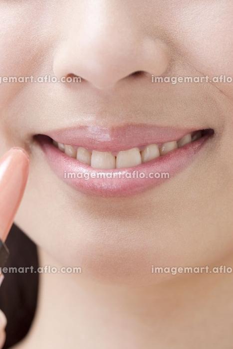 口紅を塗る女性の販売画像