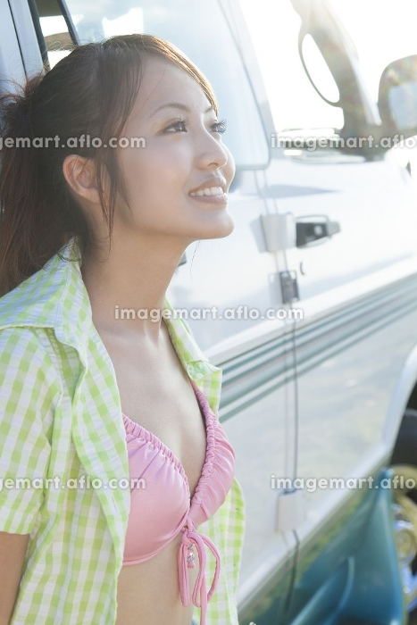 キャンピングカーにもたれる女性の販売画像
