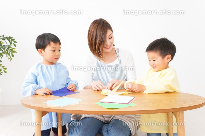 幼稚園で折り紙をする子どもと先生の販売画像