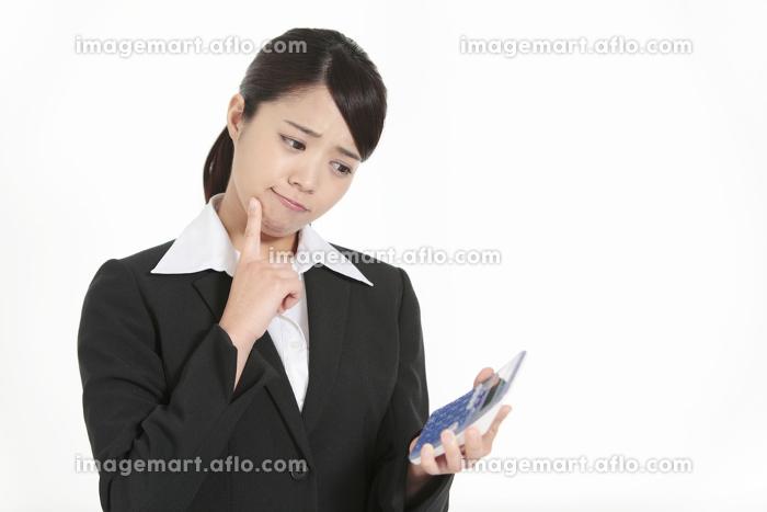電卓を持って悩むビジネスウーマンの販売画像