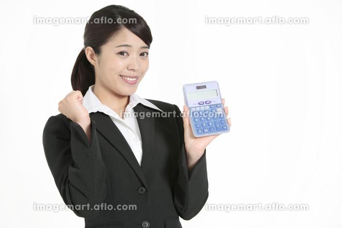 電卓を持ちガッツポーズをするビジネスウーマンの販売画像