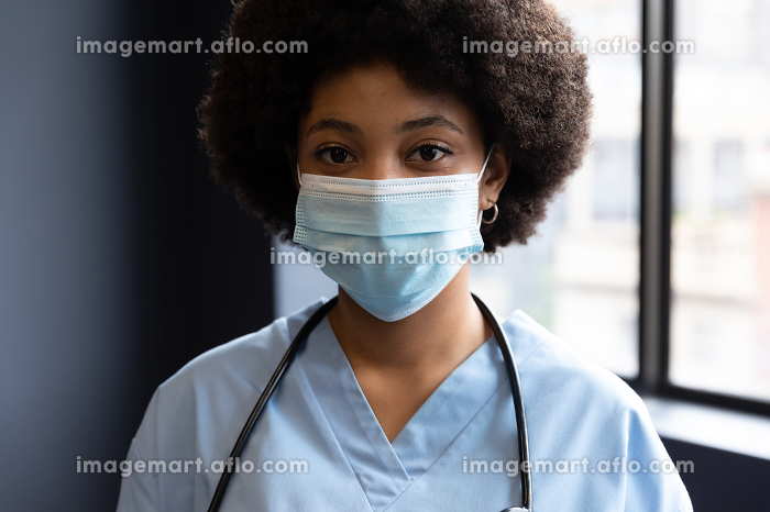 Portrait of mixed race female doctor wearing face mask. medicine healthcare professional during covid 19 coronavirus pandemic.の販売画像