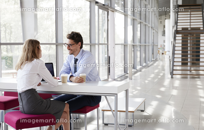 Businesswoman and businessman talking at a meeting