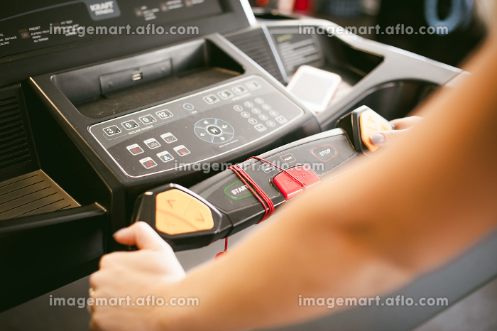 young woman is engaged fitness in gym. Performs cardio load on treadmill, running and walking with acceleration. sport, fit, lifestyle, technology and people conceptの販売画像
