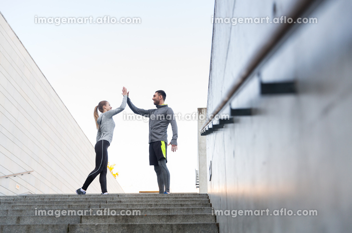 smiling couple making high five on city streetの販売画像