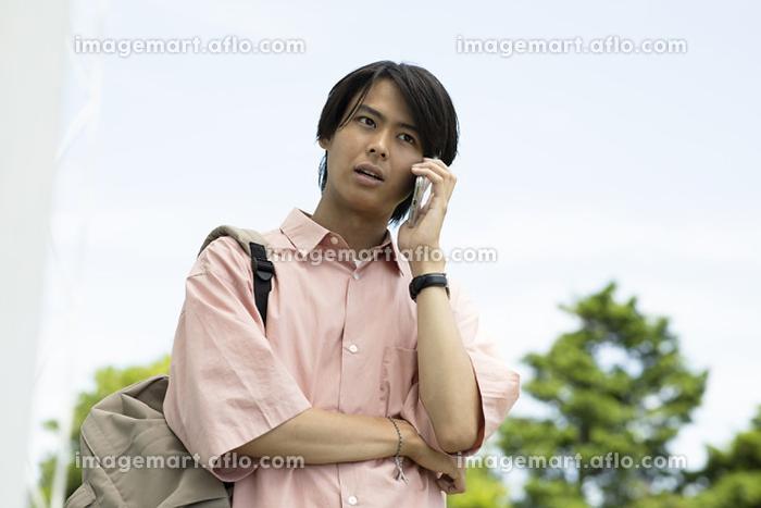 携帯電話で話す大学生の販売画像