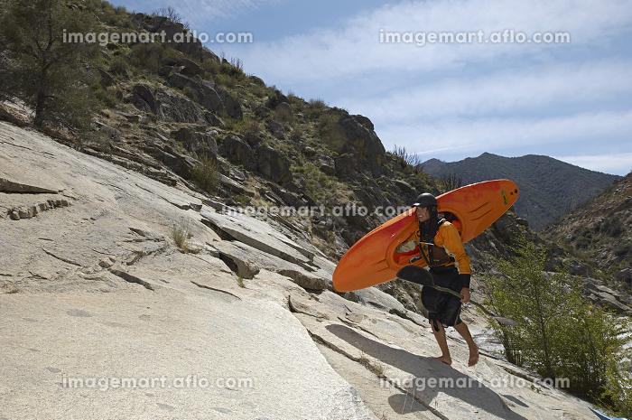 Female Kayaker Walking On Rockの販売画像