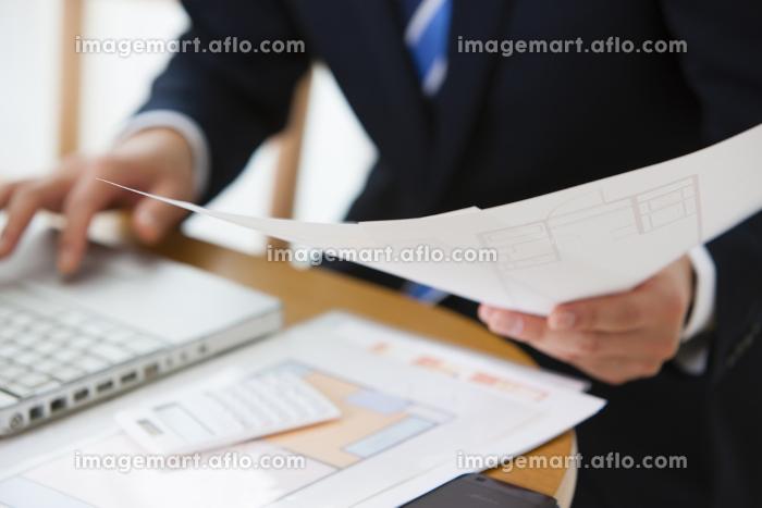 住宅間取り図面を見る男性ビジネスマンの販売画像