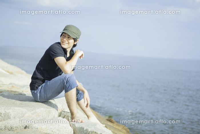 岩の上に座り水平線を眺める男性の販売画像