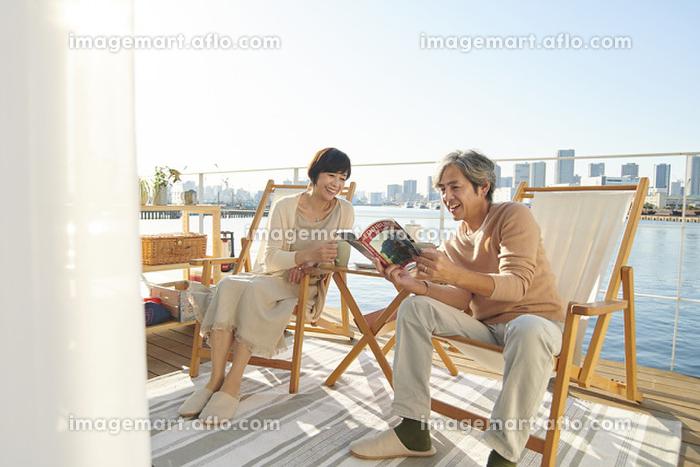 テラスでくつろぐ日本人シニア夫婦の販売画像