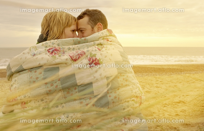 Couple cuddling under blanket on beachの販売画像