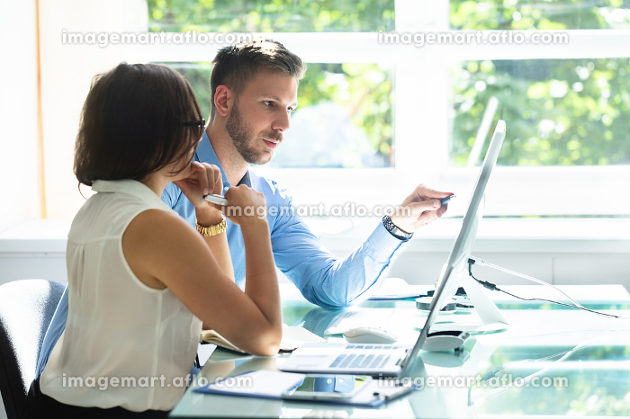 Two Businesspeople Looking At Computer Having Conversationの販売画像