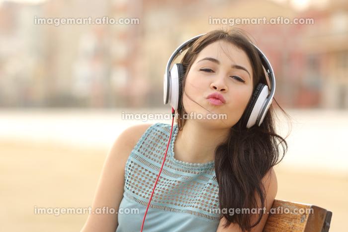 Teenager girl with headphones kissing at cameraの販売画像