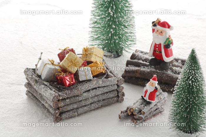 雪をかぶった木で出来た家や箱のあるクリスマスのイメージの販売画像