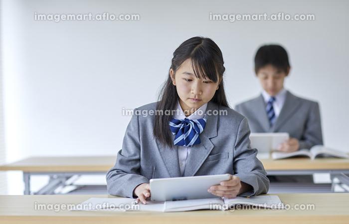 タブレットを使って授業を受ける男女の中学生