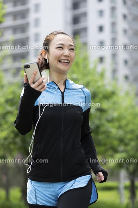 音楽を聴きながら走る女性の販売画像
