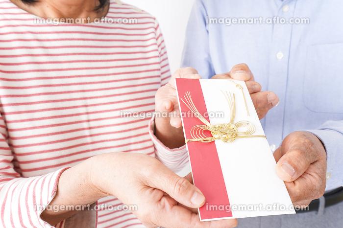 お祝いを渡すシニアの夫婦