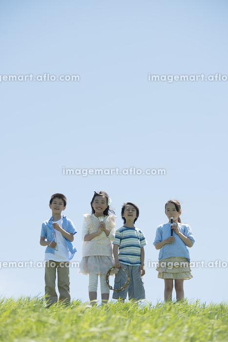 草原で楽器を持ち微笑む小学生の販売画像