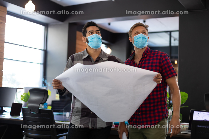 Diverse male colleagues wearing masks holding architectural plans in office. hygiene in workplace during coronavirus covid 19 pandemic.の販売画像